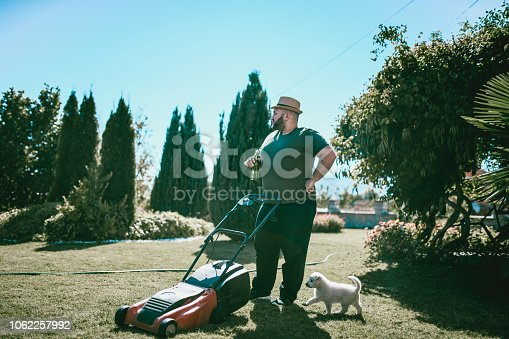 Overweight Male With Straw Hat Taking A Break Of Mowing With His Puppy And A Cold Beer