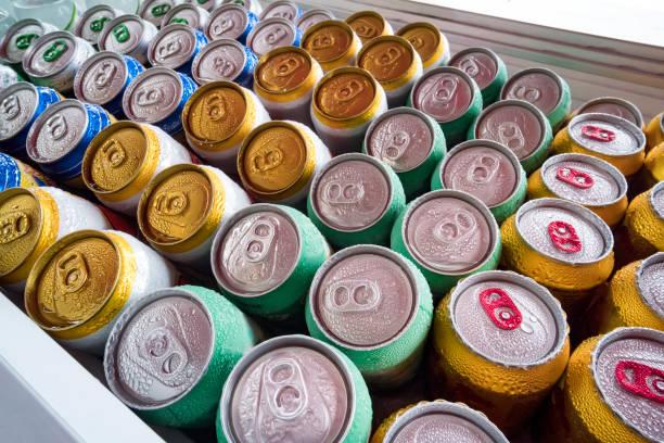 пивные банка свежие из холодильника. много алюминиевых банок во льду в открытом холодильнике. капли воды на холодной стороне напитка - напиток стоковые фото и изображения