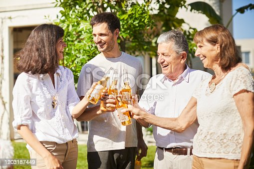 1196170672istockphoto Beer celebratory toast with the in laws in the garden. 1203187449