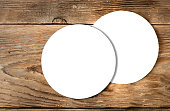 White coasters isolated on wooden background. Ready mock up of blank round mat for brewery design, advertising, brand representing