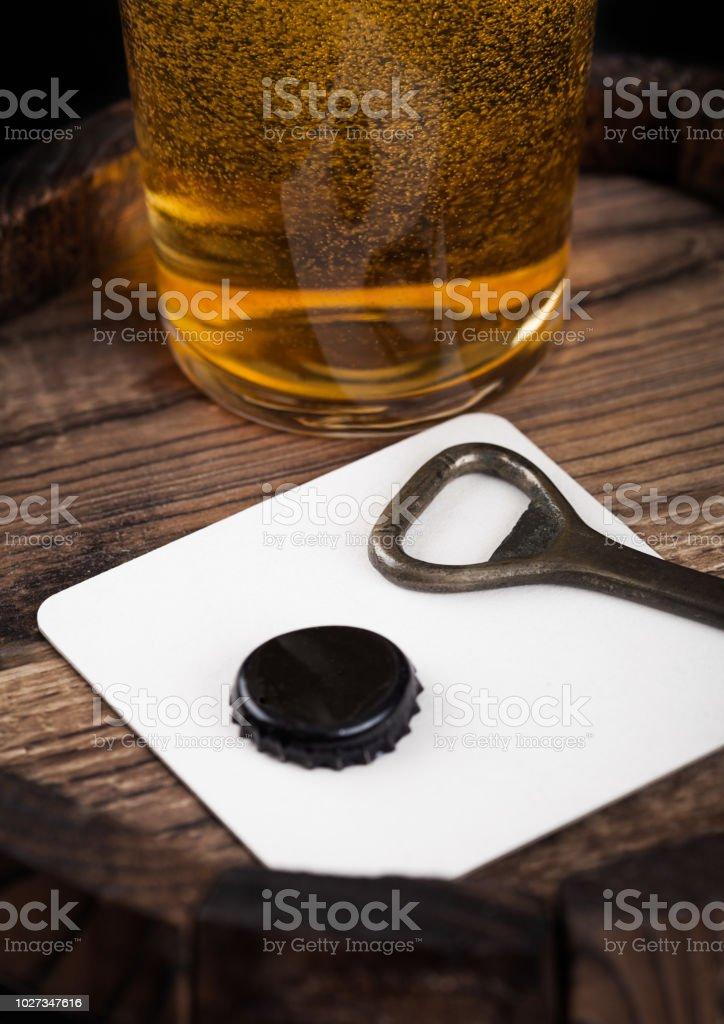 Posavasos de cerveza con abrelatas, superior de la botella y vaso de cerveza en barril de madera. - foto de stock