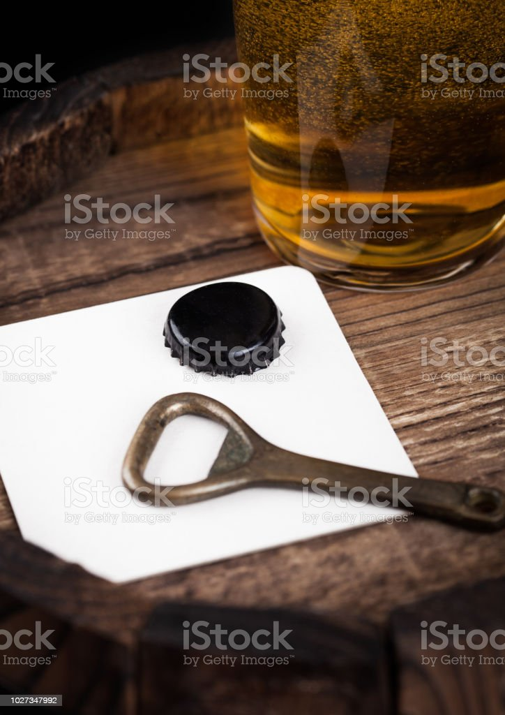 Beer coaster with bottle top and opener and glass of beer on top of wooden barrel. stock photo