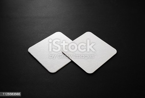 Blank square beer coasters mockup on black background.