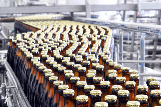 beer filling in a brewery - conveyor belt with glass bottles stock photo