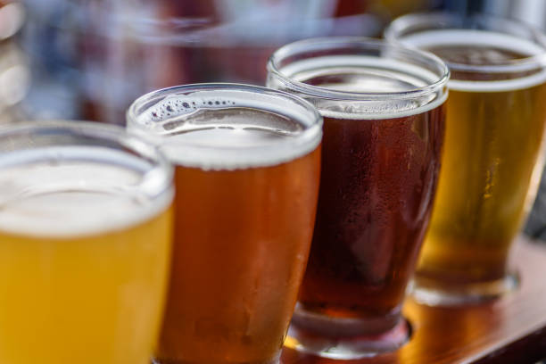 Beer flight in summer sunlight Beautiful colorful beer sample glasses at microbrewery beer glass stock pictures, royalty-free photos & images
