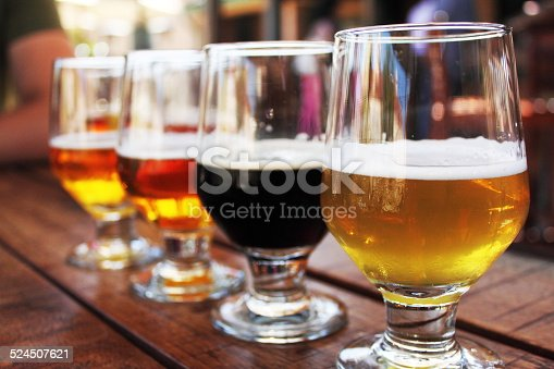 Flight of four beers lined up on a wooden table, with selective focus on the  first beer. Photo taken outdoors with natural lighting; beers range in color from light to very dark. Background out of focus.