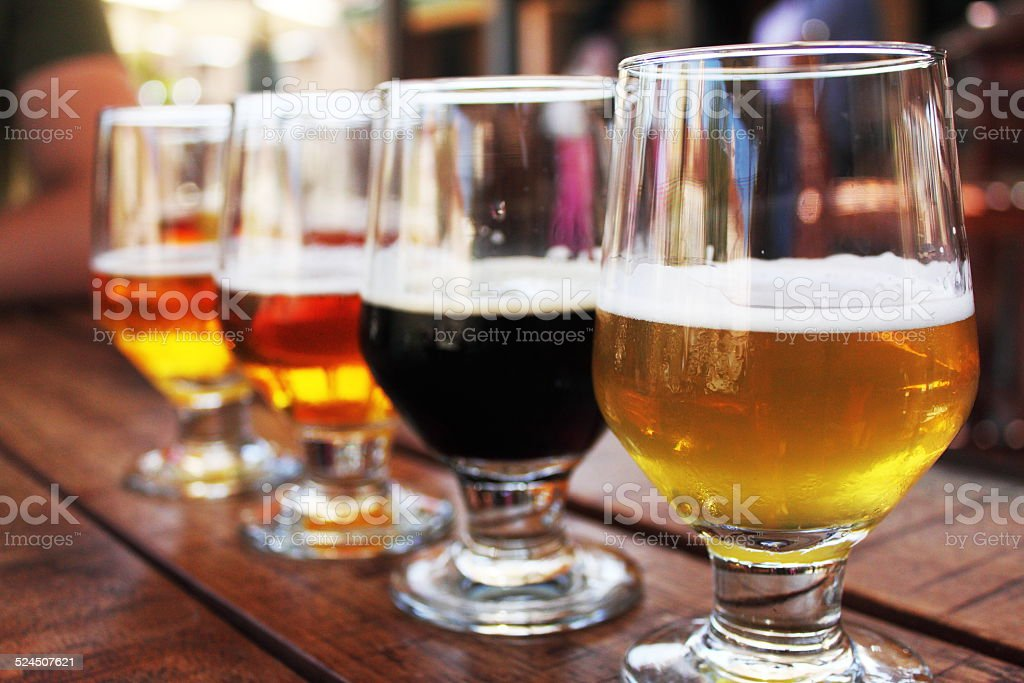 Beer Flight of four beers in glasses stock photo