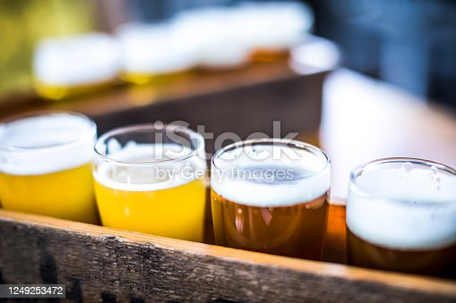 Flight of four beers lined up on a wooden table, with selective focus. Photo taken outdoors with natural lighting; beers range in color from light to very dark. Background out of focus.