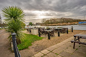 Riverside beer garden on the bank of the River Bure with selective focus on the black metal post and fence, and the green bush