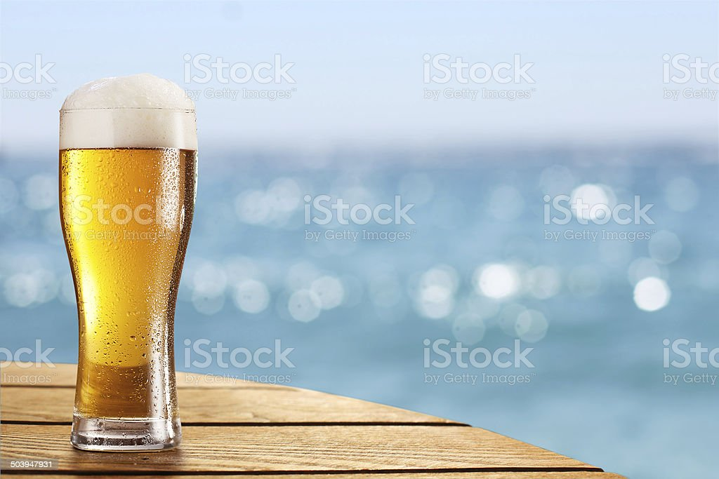 Beer glass on a blurred background of sea. stock photo