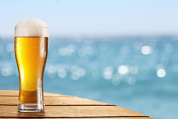 Birra in vetro su sfondo sfocato di mare. - foto stock