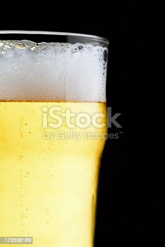 A single beer glass over a black background.