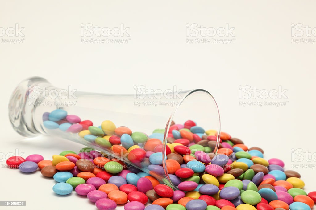 beer glass spilling colored candy chocolate beans plain background royalty-free stock photo