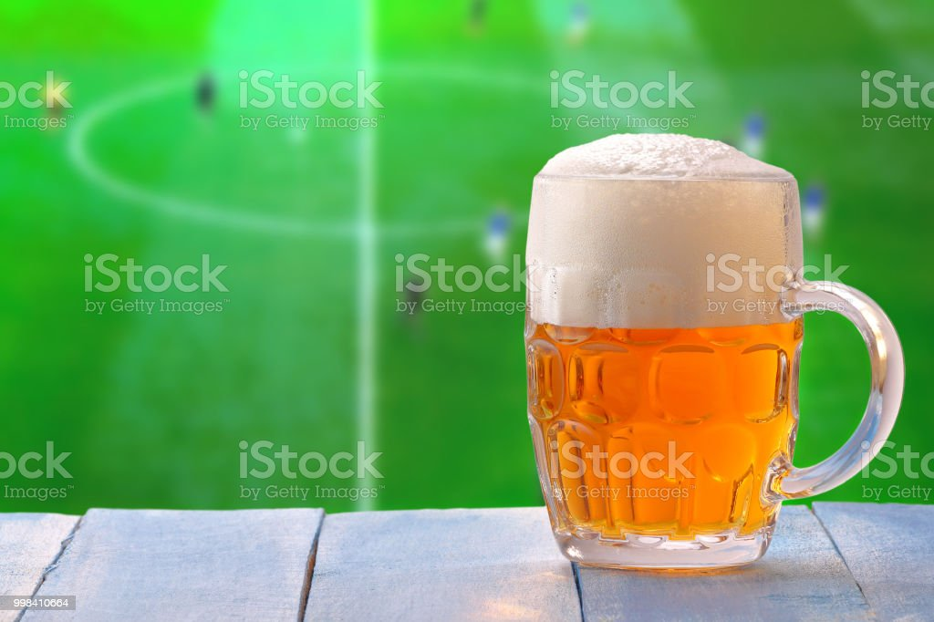 Beer glass with foam and against tv background – zdjęcie