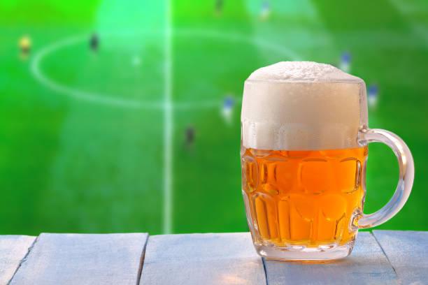 Bierglas mit Schaum und TV-Hintergrund – Foto