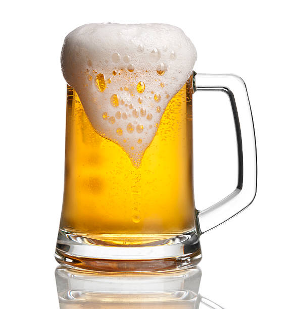 Beer glass with overflowing foam photographed overflowing beer mug with a bit of condensation. clipping path included. View more drinks beer glass stock pictures, royalty-free photos & images