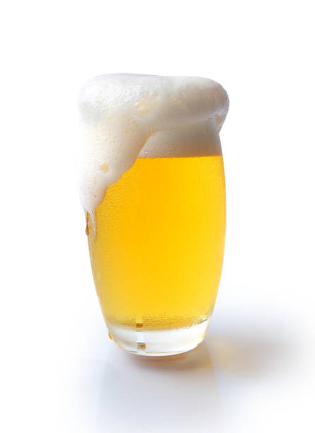 beer glass with overflowing foam - beer foam stock photos and pictures