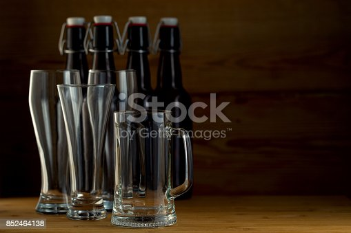 913660896istockphoto Beer glasses and beer bottles on a wooden background 852464138