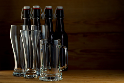 913660988 istock photo Beer glasses and beer bottles on a wooden background 852464138