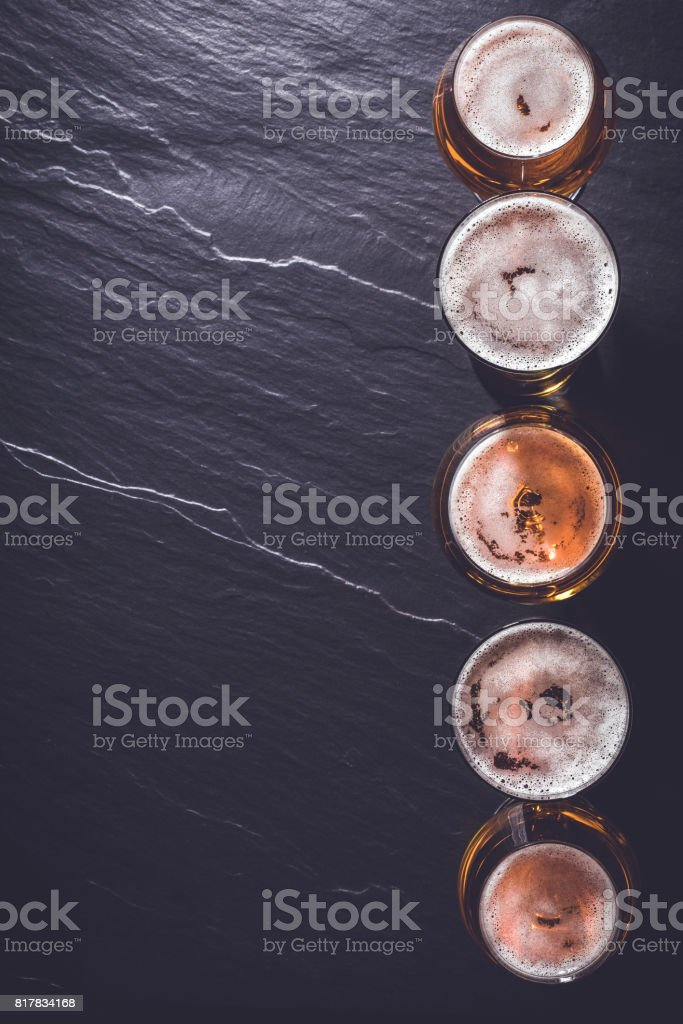 Beer glasses on dark gray stone background. stock photo