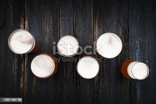 Beer glasses on dark wooden table with space on text