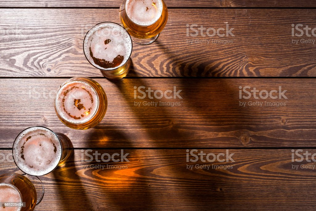 Beer glasses on wooden table stock photo