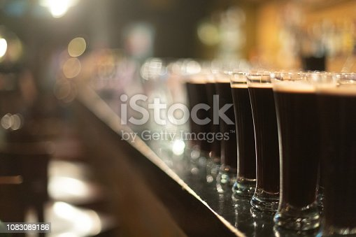 913660896 istock photo Beer glasses with dark beer are on the bar counter 1083089186