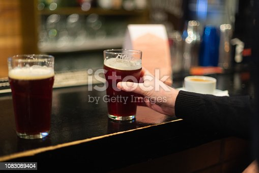 913660988istockphoto Beer glasses with dark beer are on the bar counter 1083089404