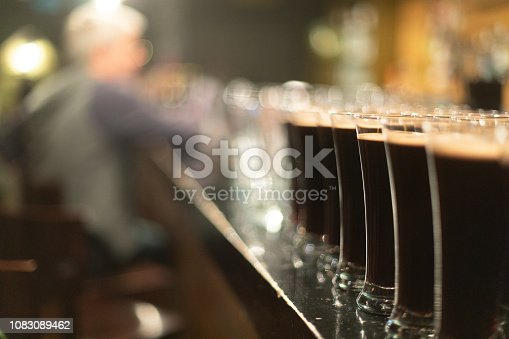 913660988istockphoto Beer glasses with dark beer are on the bar counter 1083089462