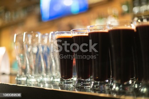 913660988istockphoto Beer glasses with dark beer are on the bar counter 1083089536