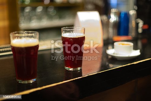 913660896 istock photo Beer glasses with dark beer are on the bar counter 1083089550