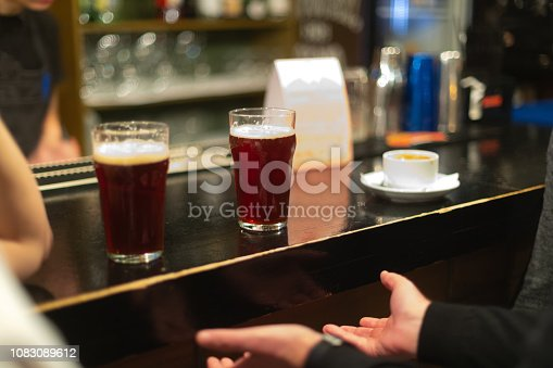 913660988istockphoto Beer glasses with dark beer are on the bar counter 1083089612