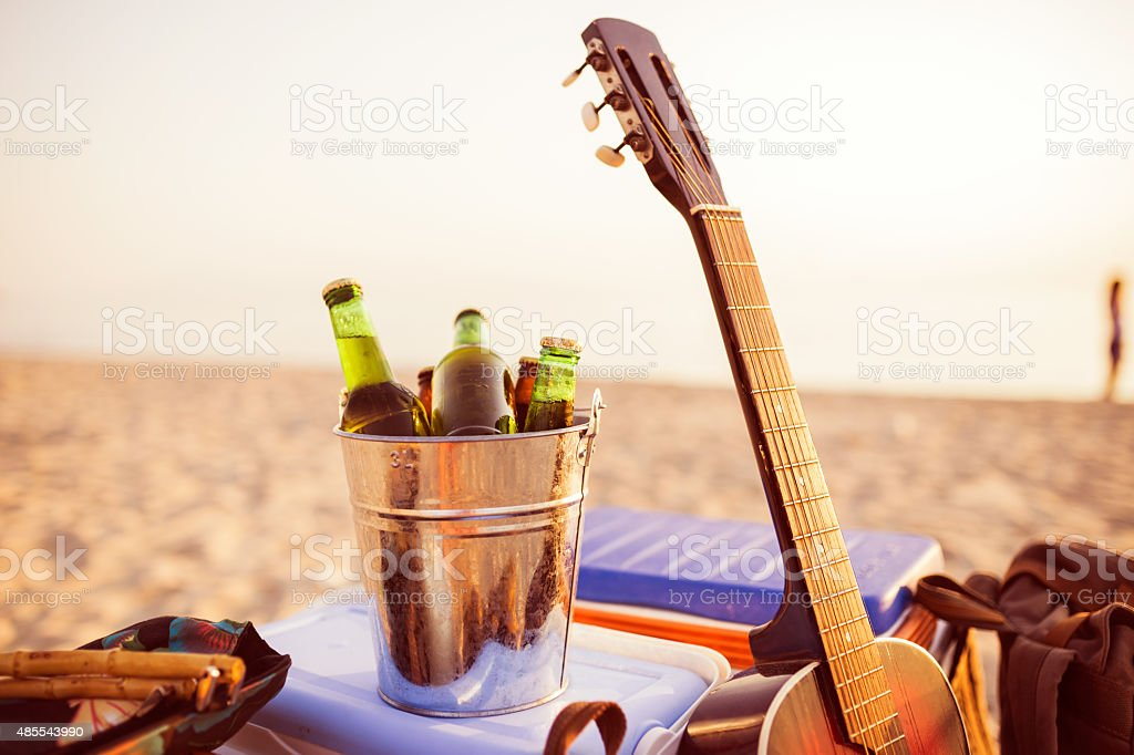 Beer in a bucket of ice on a beach. stock photo