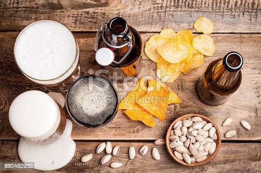 istock Beer in bottles and glasses on a wooden table. Beer and snacks are pistachio nuts, chips and nachos. Drink and snack for the football match or party 692452932
