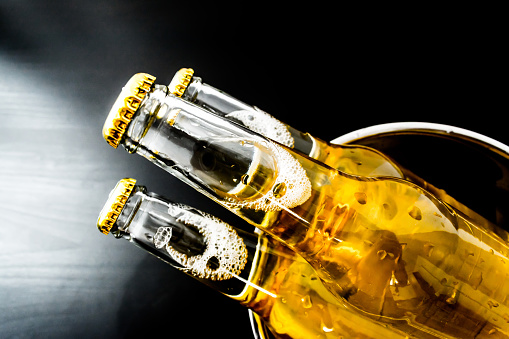 istock Beer in bottles with bubbles closeup on dark background 836602432