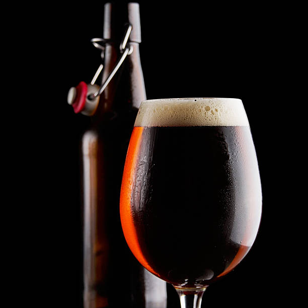 Beer in glass on a black background stock photo