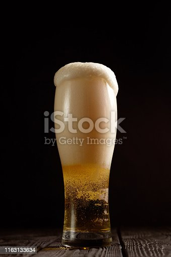 1073474208istockphoto beer in glass on black background,  foam pours out of the glass 1163133634