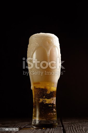 1073474208istockphoto beer in glass on black background,  foam pours out of the glass 1166167872
