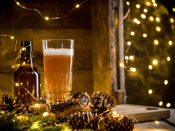 Beer in glass on wooden background with Christmas lights and pine cones Beer in glass on wooden background with Christmas lights and pine cones. Studio shot beer stock pictures, royalty-free photos & images