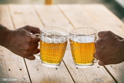 istock Beer in glasses big and glass light Golden with foam and hands of friends close-up 1051223336