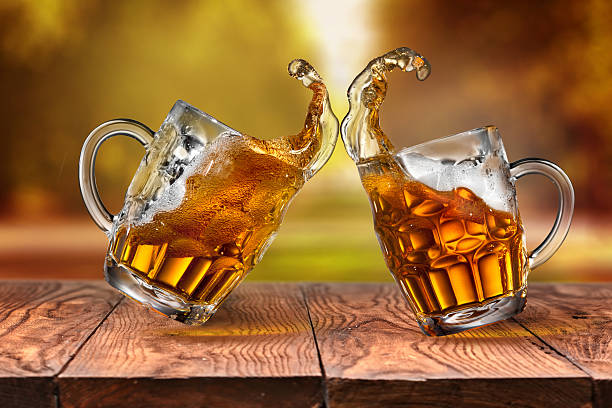 Beer in glasses with splash on wooden table stock photo