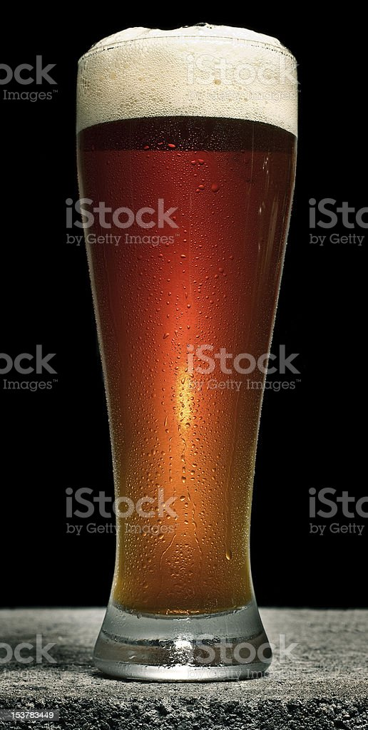 Beer in Pilsner Glass on Concrete with Head stock photo