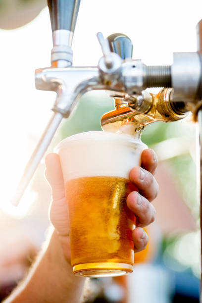 beer is poured into a glass from a tap. The bartender pours beer into a plastic glass stock photo
