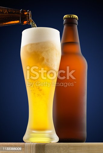 Beer is poured into a glass on the background of a bottle and a round blue gradient