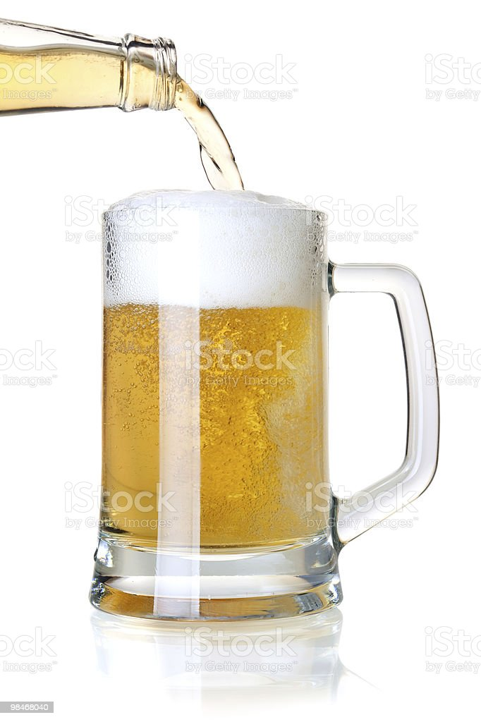 Beer is pouring into a glass from bottle royalty-free stock photo