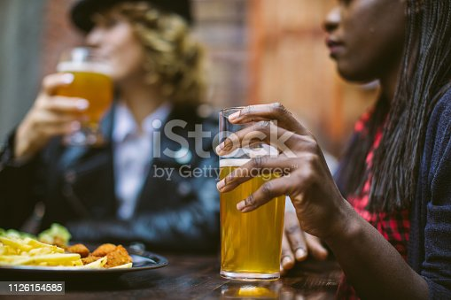 Close up of two women holding beer glasses while sitting in cafe at weekend