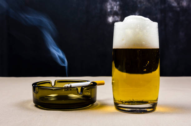 Bira bardağı ve yanan sigara. stok fotoğrafı