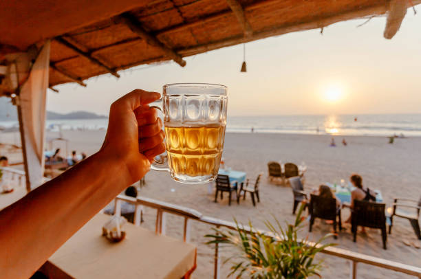 Beer mug in hand of tourist relaxing on a beach with lounge and some cafe outdoor of Asia Beer mug in hand of tourist relaxing on a beach with lounge and some cafe outdoor of Asia. goa stock pictures, royalty-free photos & images