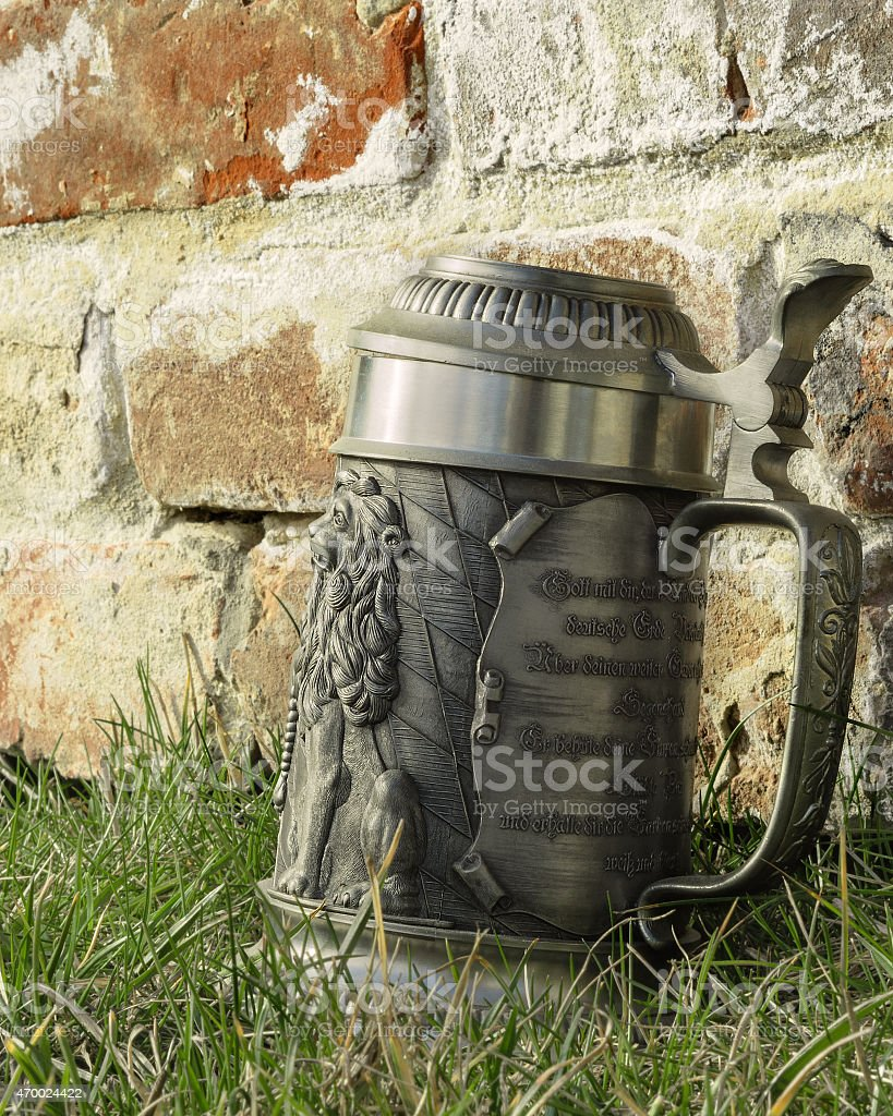 beer mug on the grass near the brick wall stock photo