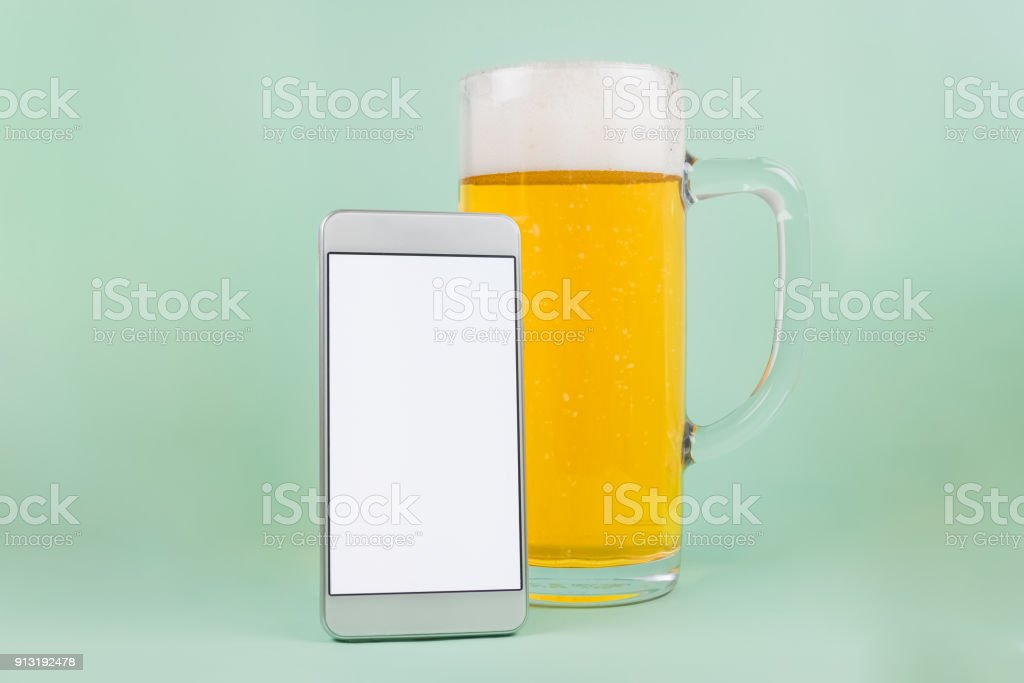 Beer mug with froth and white blank screen smartphone. Space for copy. stock photo